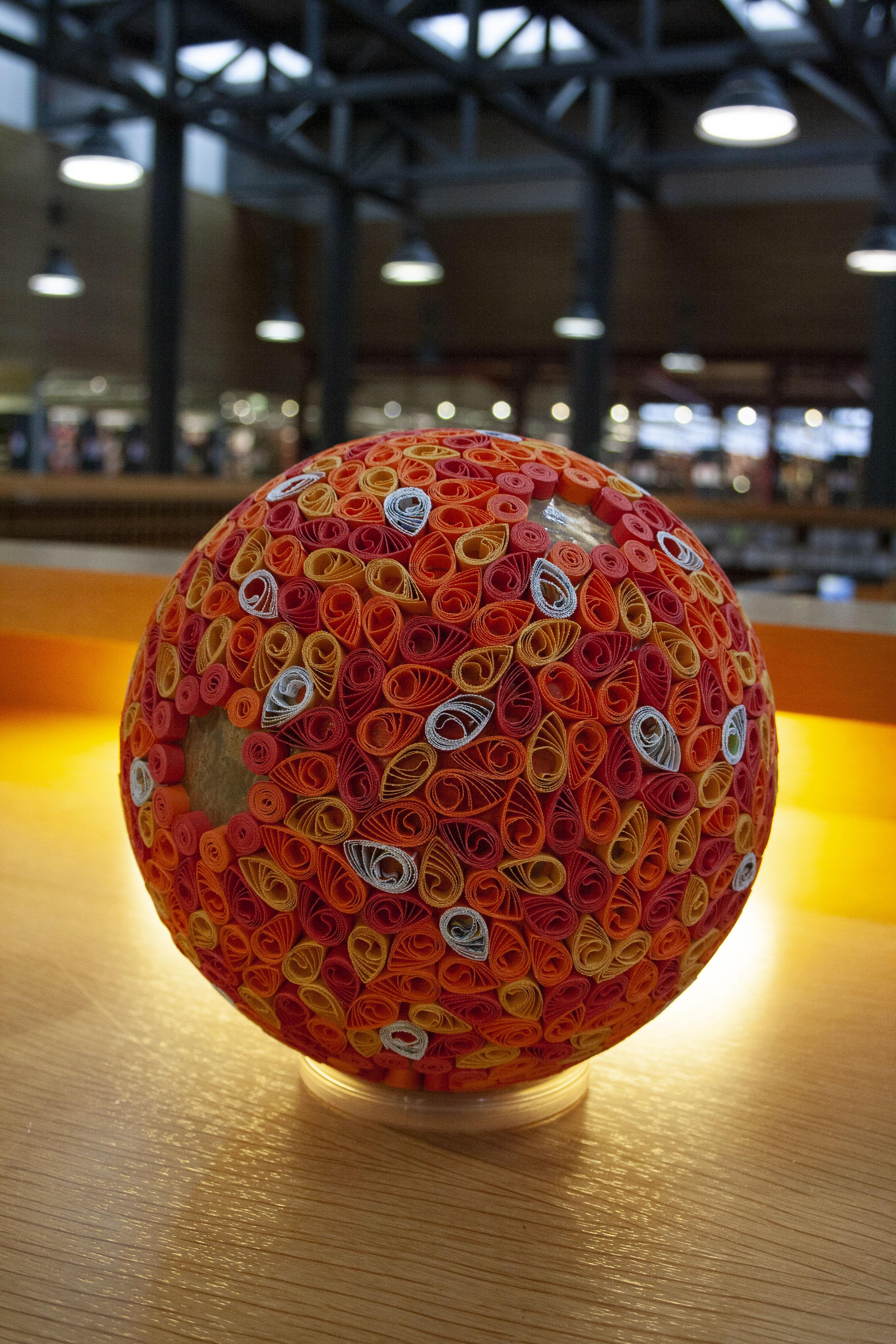 Eine große Kugel, in rot-orange-Tönen gehalten, von hinten angeleuchtet.