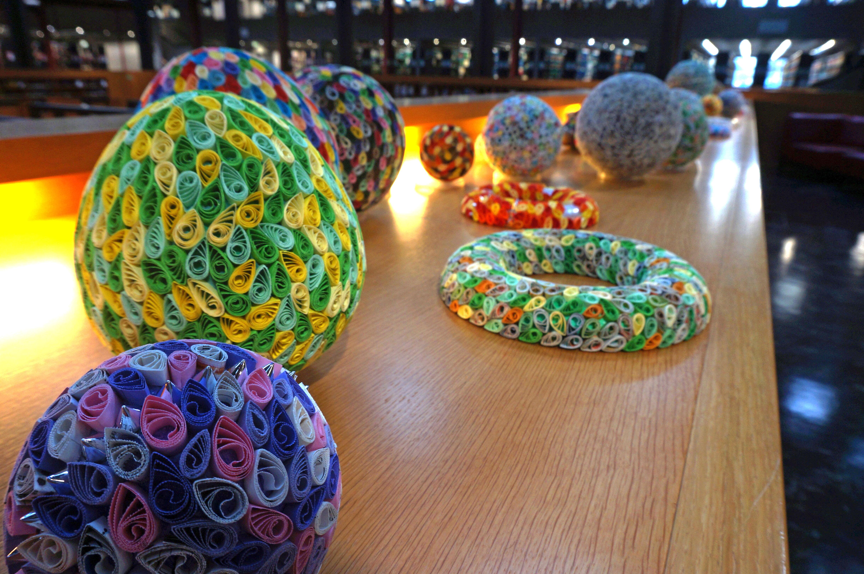 Mehrere Objekte, darunter ein großes Ei in gelb-grün und eine Kugel in rosa-lila-Tönen und silbernen Spitzen.
