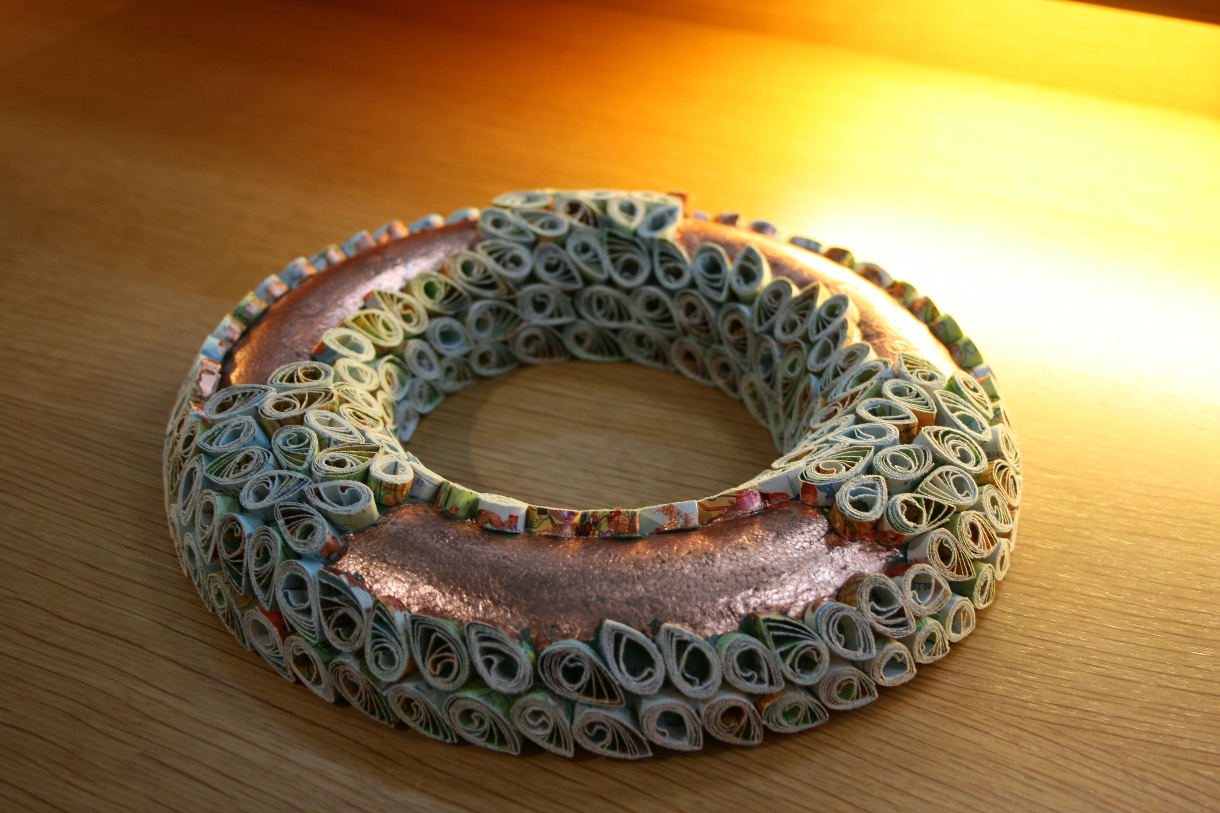 Ein Ring, teilweise mit weißen Elementen verziert, die freien Stellen sind mit bronzefarbener Farbe gestaltet.