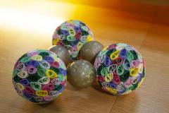 Aus drei mit der tropfenform bunt gestalteten Kugeln und drei grau lackierten Kugeln entsteht eine Form, die an ein Molekül erinnert.